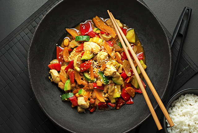 Chinese food with meat and vegetables on black background